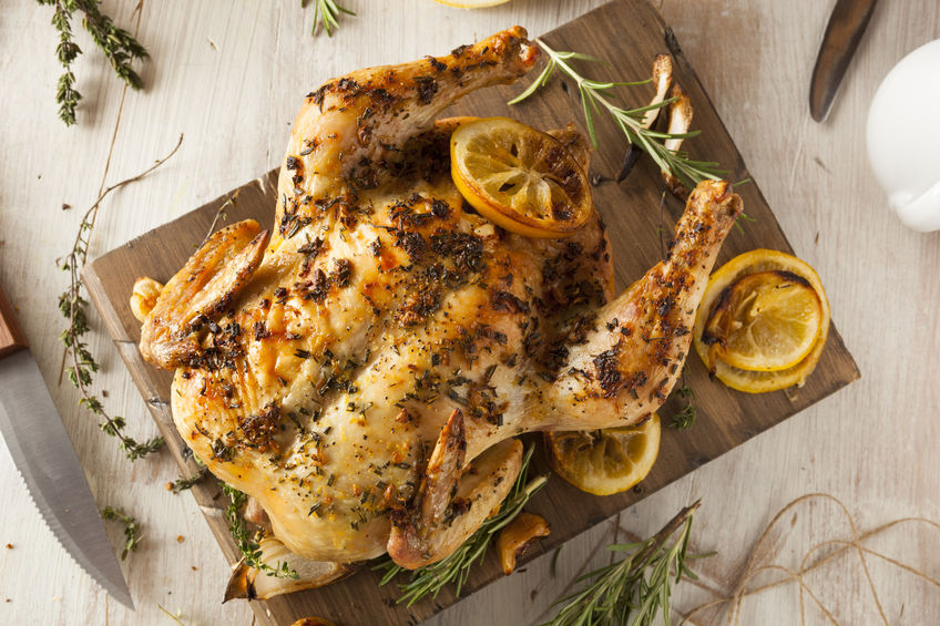 37578763 - homemade lemon and herb whole chicken on a cutting board