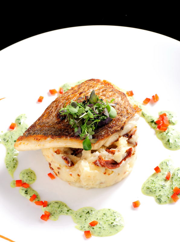 40909144 - tasty healthy fish fillet with potato puree with dried tomatoes and wild garlic sauce